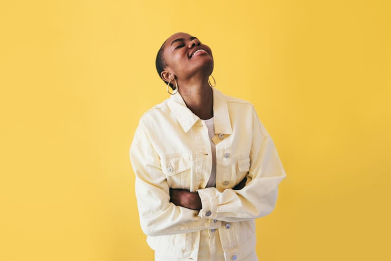 Happy Woman Wearing Yellow on a Yellow Background