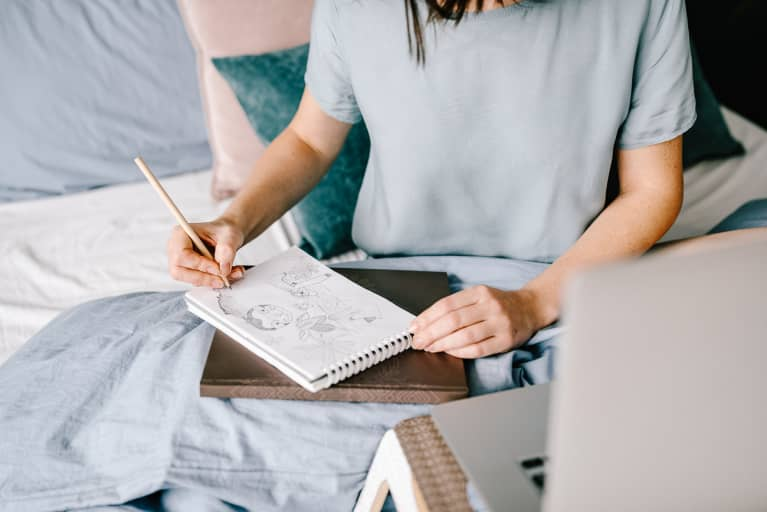 Unrecognizable female sitting on comfortable bed and drawing sketch in notepad while working at home