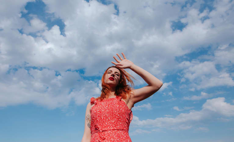 Young woman feeling groggy with a blue sky background