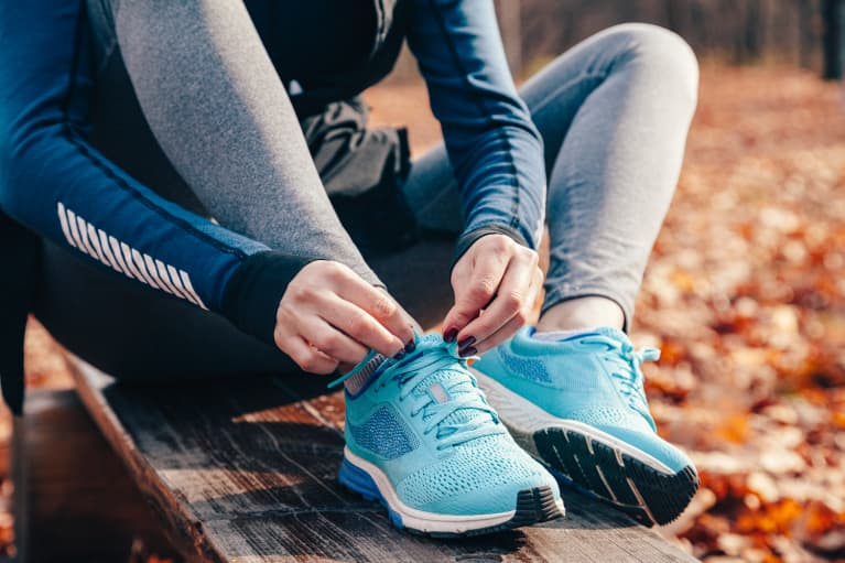 Woman Tying Running Shoes on an Outdoor Run