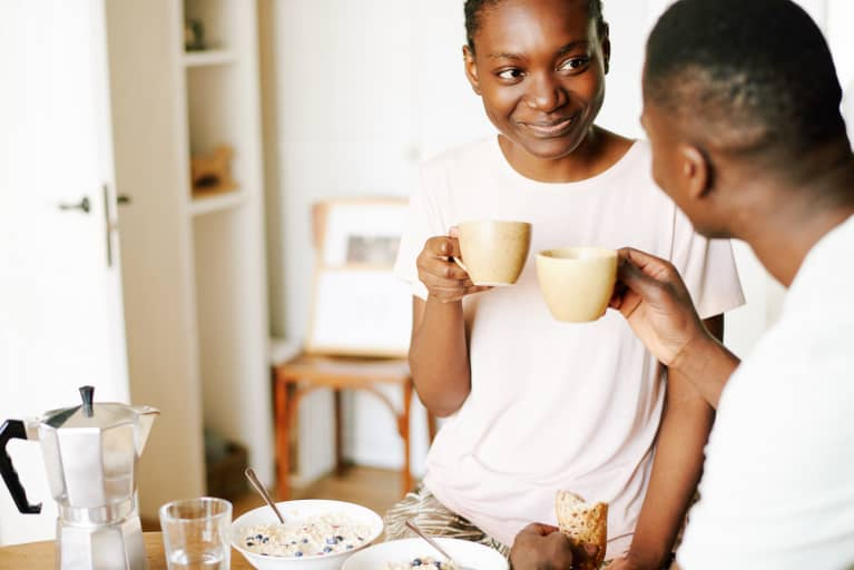 woman sitting in kitchen with her boyfriend, having tasty healthy breakfast, drinking coffee and smiling cheerfully
