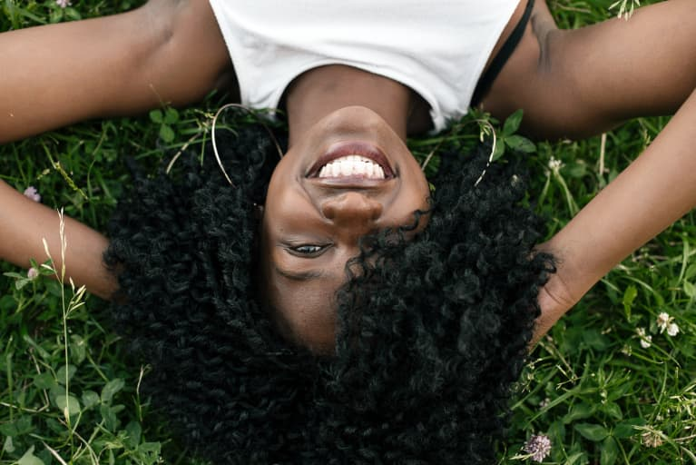 girl with curls laying down in the grass