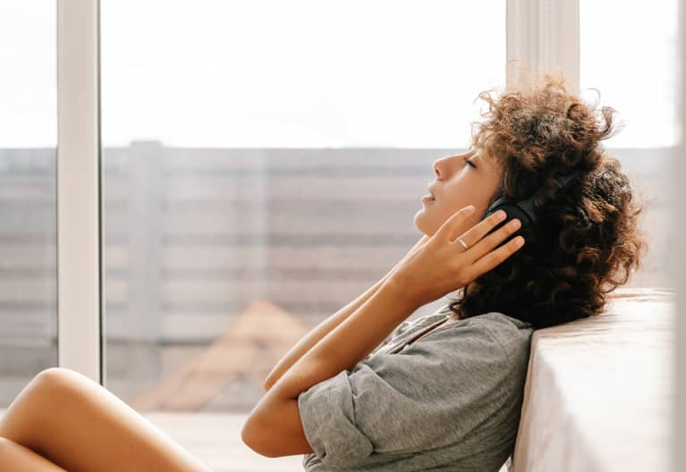 Woman Listening To Music Near Bed