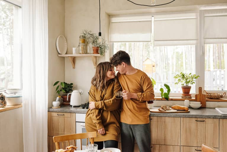 Married couple in love wearing casual outfit spending time together standing in modern kitchen