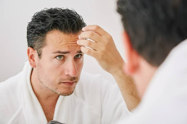 Man Checking His Hair in the Mirror