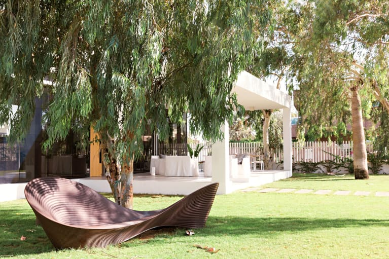 white awning surrounded by grass and an oversized lounge chair