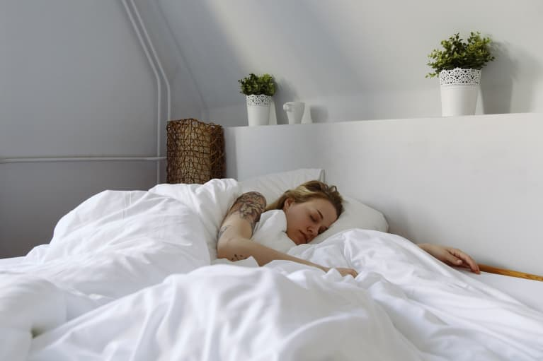 young woman sleeping in white bedroom with plants over bed