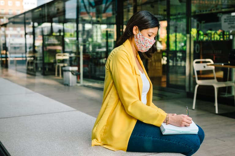 Woman Sitting Outdoors in Business Attire and a Face Mask Journaling