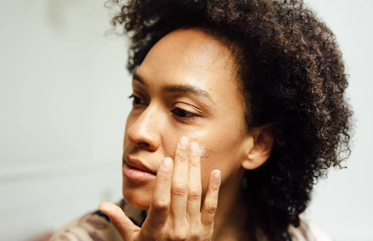 Close Up Of A Woman Putting Lotion On Her Face