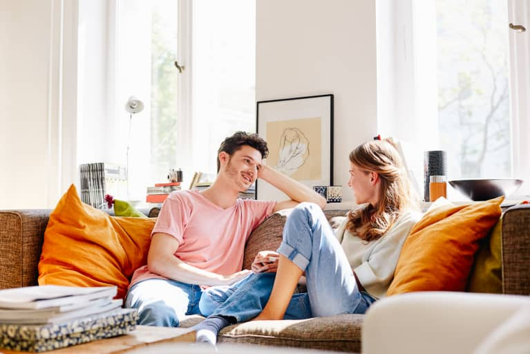 Happy Young Man Talking With Woman On Sofa At Home