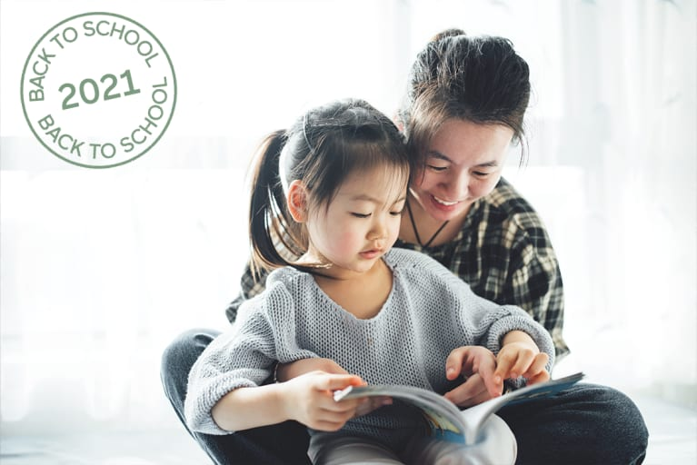 Young Asian mother and her toddler cute girl reading books at home