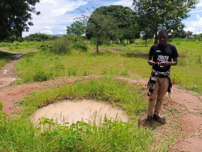 man standing next to a small, dirty pond in grassy field