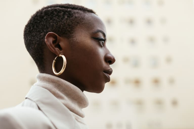 Thoughtful Young Woman Wearing a Turtleneck, Blazer, and Gold Earrings