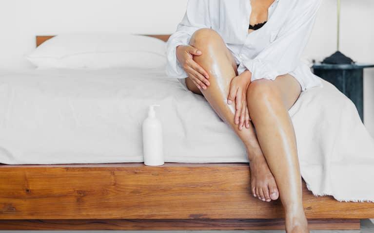Woman applying lotion on legs