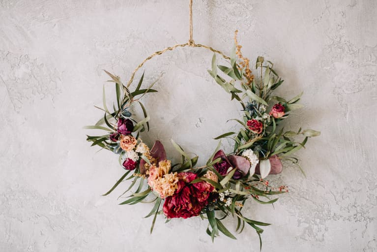 Summer Wreath of Dried Flowers and Greens Hanging on a Wall