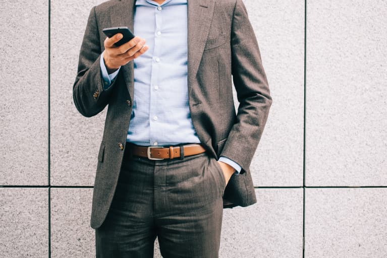 Casual Business Man Looking At His Phone With His Hand In His Pocket