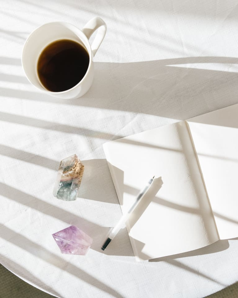 Crystals On Table With Coffee Cup, Pen, And Notebook