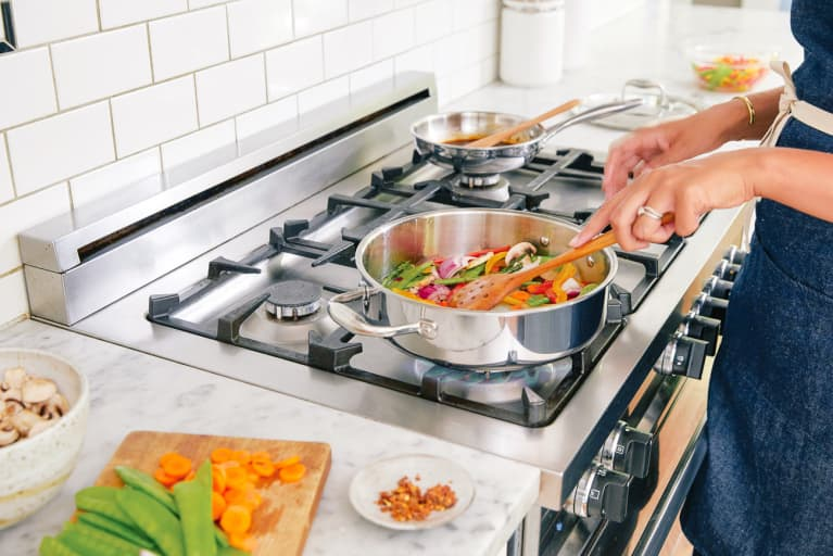Woman Cooking a Healthy Plant Based Meal on a Gas Stove