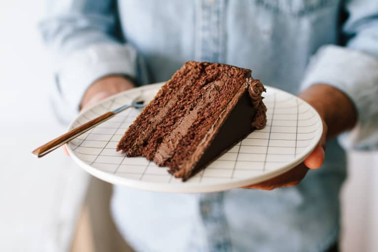 Man Holding a Plate with a Slice of Chocolate Cake