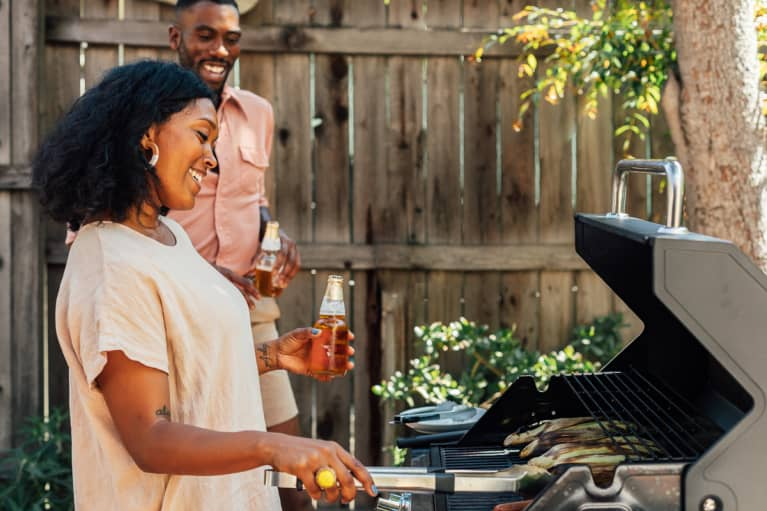 Woman Grilling in Her Backyard While Holding a Drink