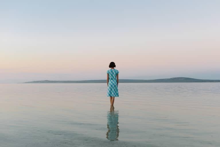 Woman Walking Along Shallow Water