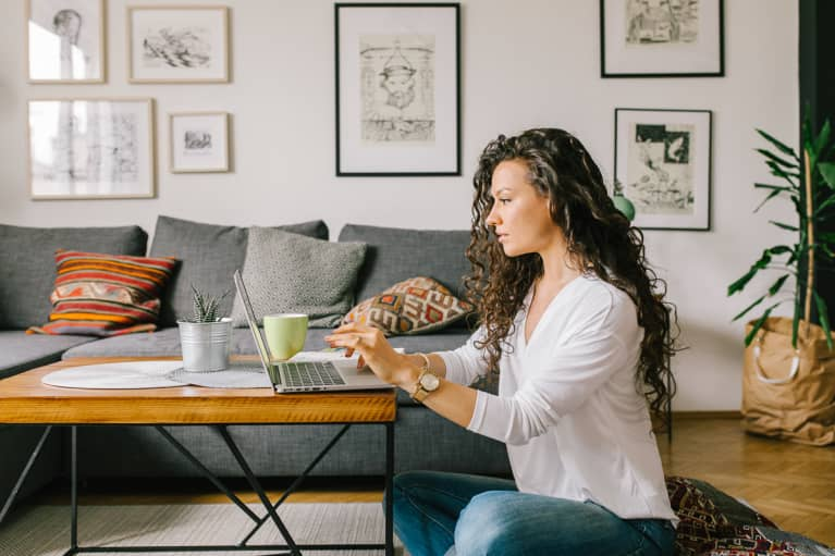 Woman Working Remotely At Her Living Room Coffee Table