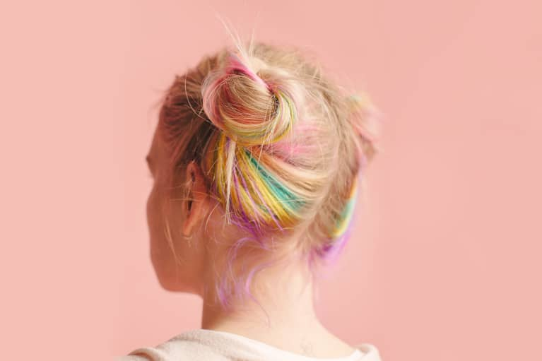 Woman with colorful hair on pink background