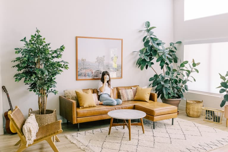 Woman Sitting on a Couch Drinking Coffee in Her Clean, Brightly Lit Living Room