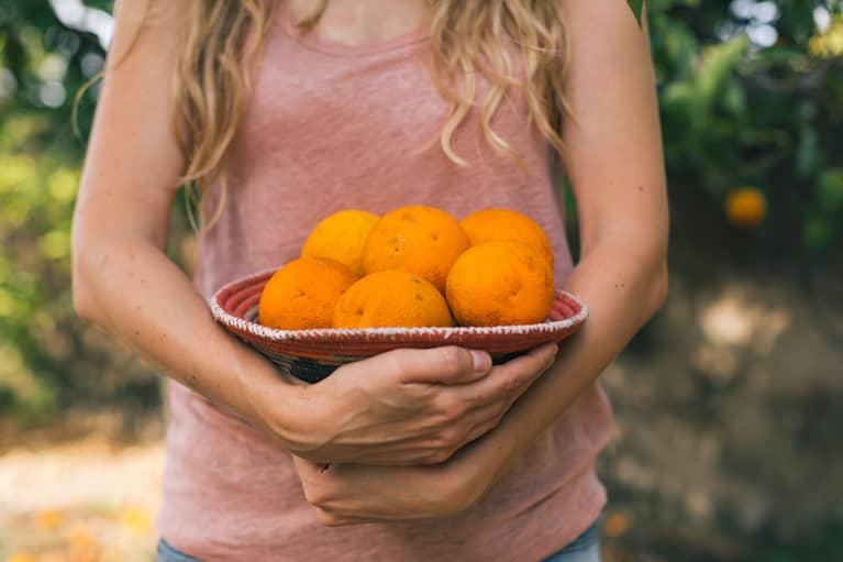 Woman Taking Orange From The Garden