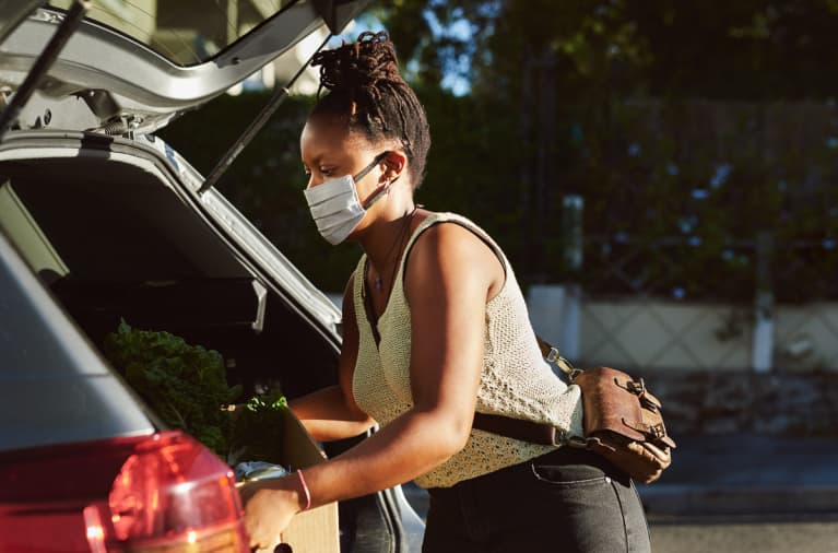 Woman Unloading Groceries From Her Trunk While Wearing a Medical Face Mask