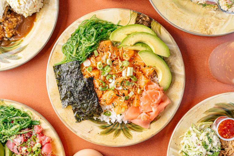 Raw salmon poke bowl with white rice, scallions, seaweed salad, avocado, ginger, and nori