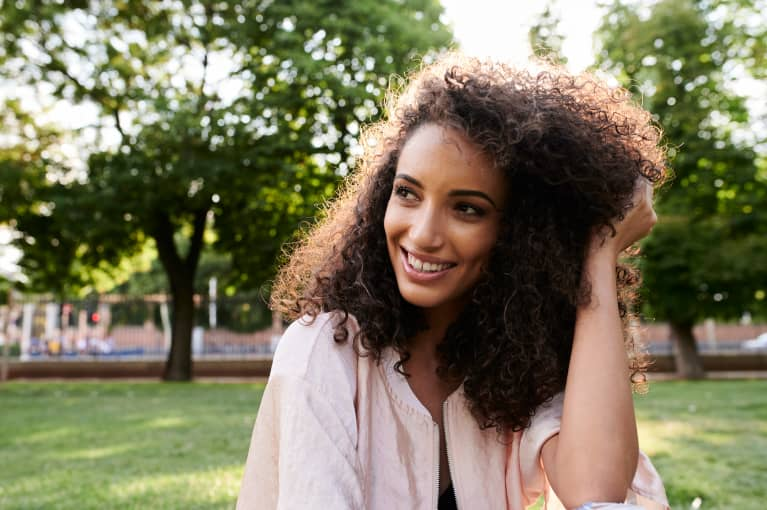 woman smiling with lush, curly hair