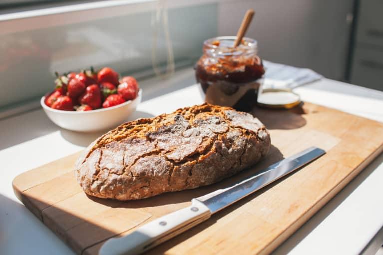 Fresh Loaf of Bread on a Cutting Board with a Jam Jar
