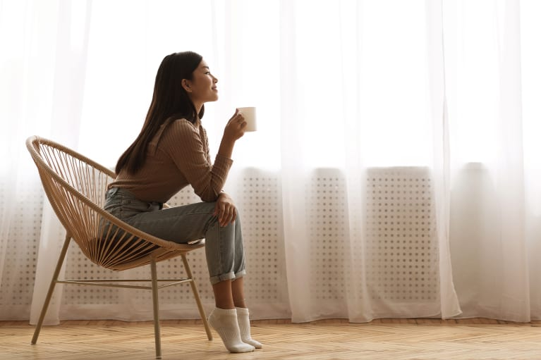 Young asian woman drinking a cup of coffee with curtains in the background