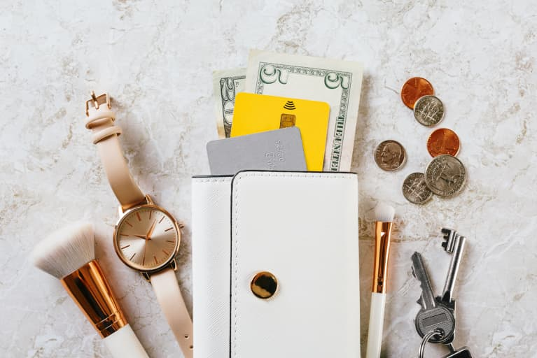 Wallet, Watch, Keys, Coins, and Makeup Brushes on a Marble Background
