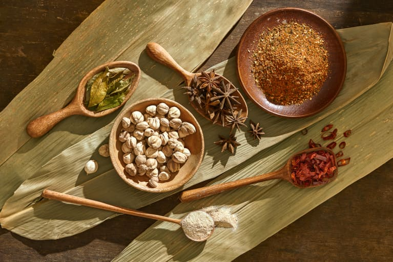 Various herbs and spices on spoons and plates on wooden background