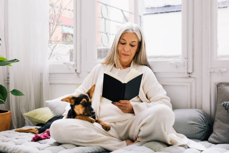 Woman Reading a Book in a Cozy Corner at Home with Her Puppy