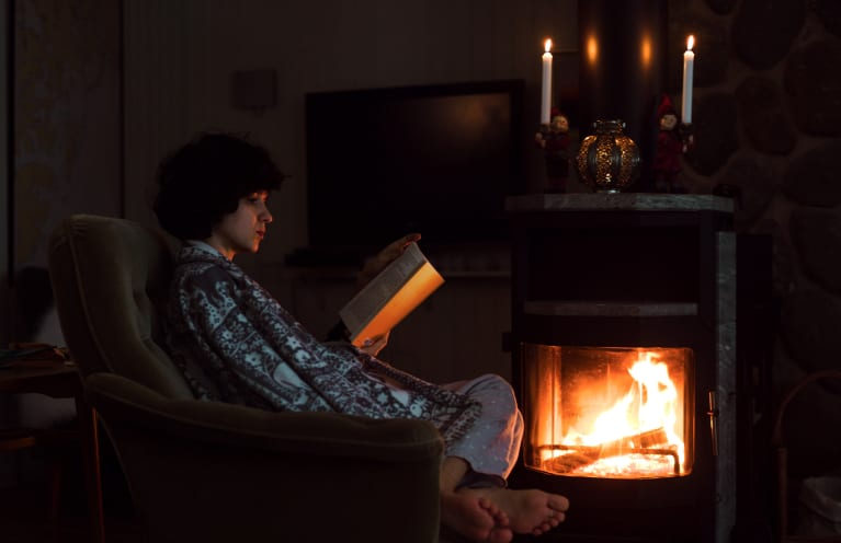 Young Woman Is Reading Book Near The Fireplace