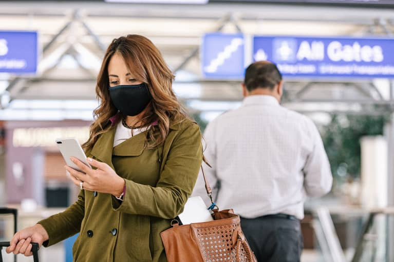 Woman Checking Her Phone At The Airport During COVID-19