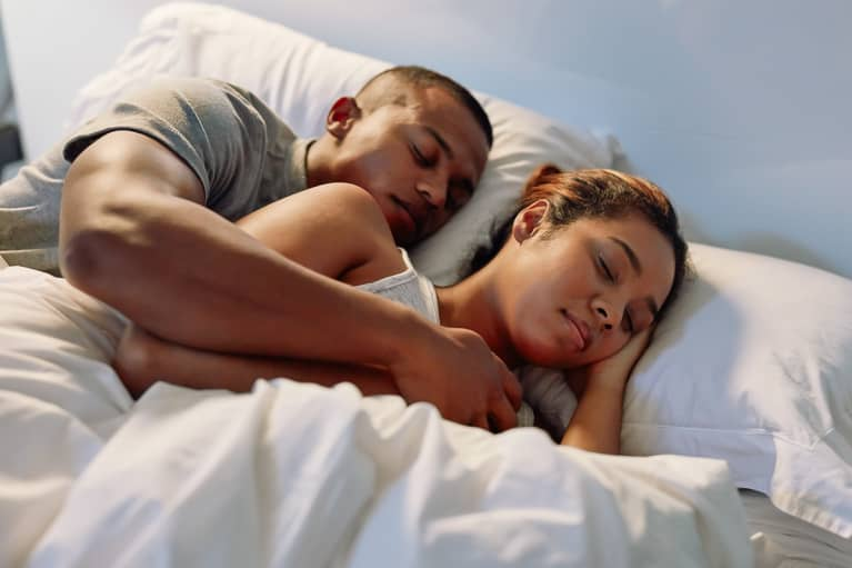 Couple Snuggled Up and Sleeping In Bed