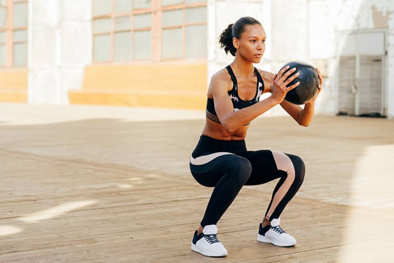 Fit Woman Doing a Squat with a Medicine Ball