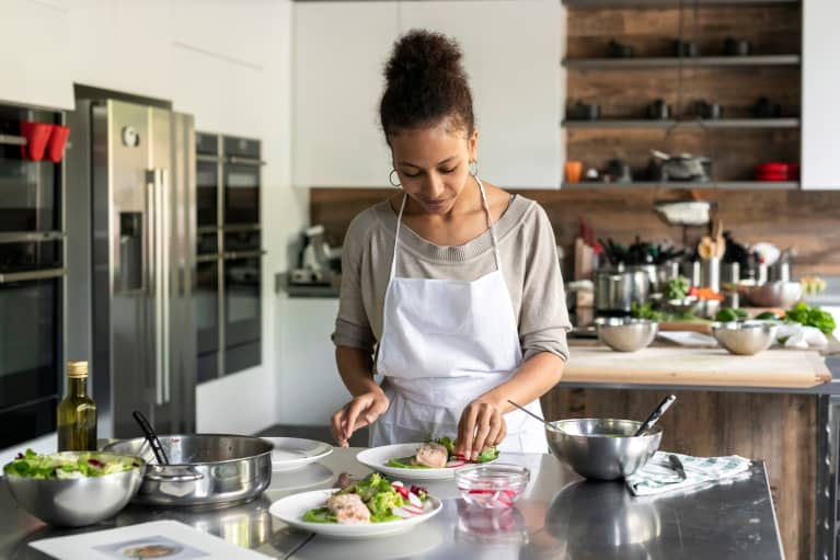 Young black or multiracial woman cooking in the kitchen