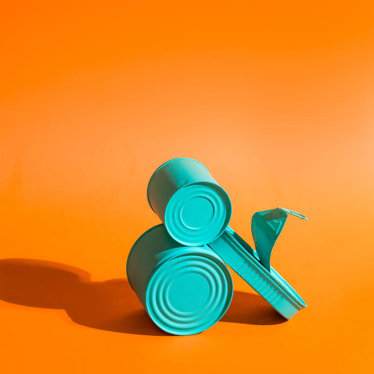 Painted Blue Tin Cans on an Orange Background