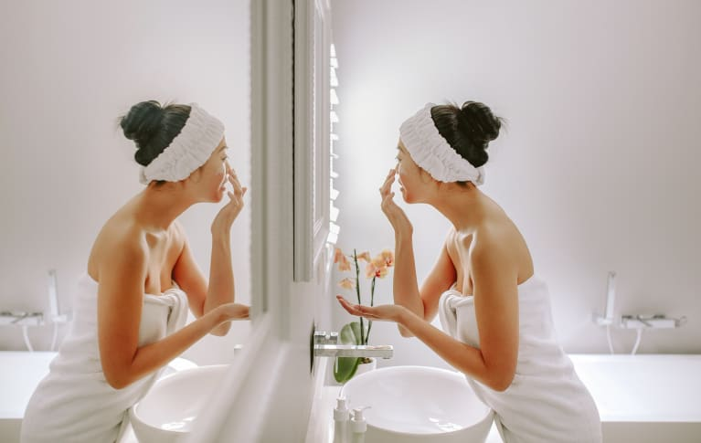 Young woman applying facial cleanser in the bathroom mirror