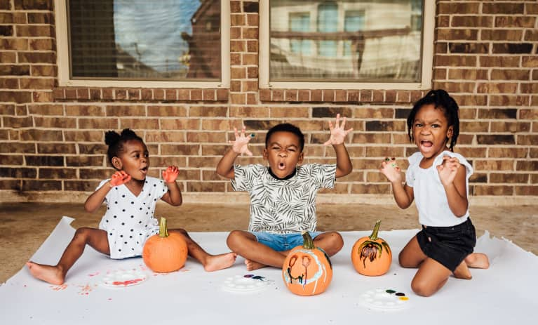 Kids sitting on back porch painting pumpkins