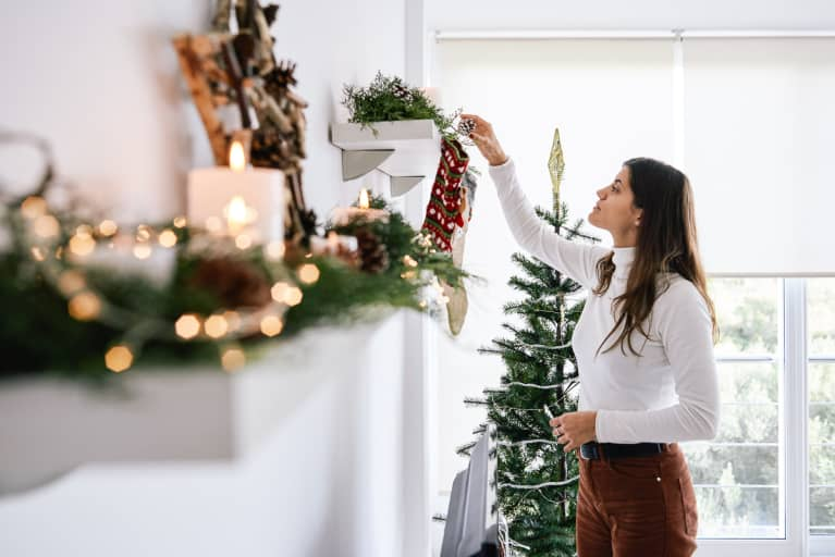 Young Woman at Home Putting Up Holiday Decorations