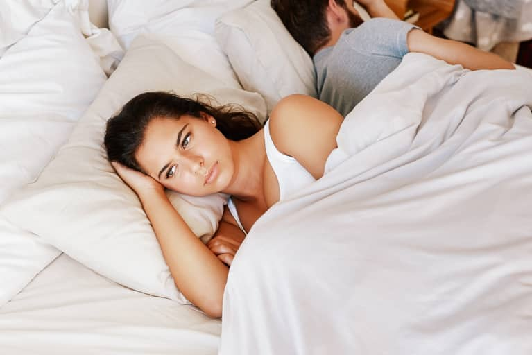 Upset Woman Turned Away From Her Partner in Bed