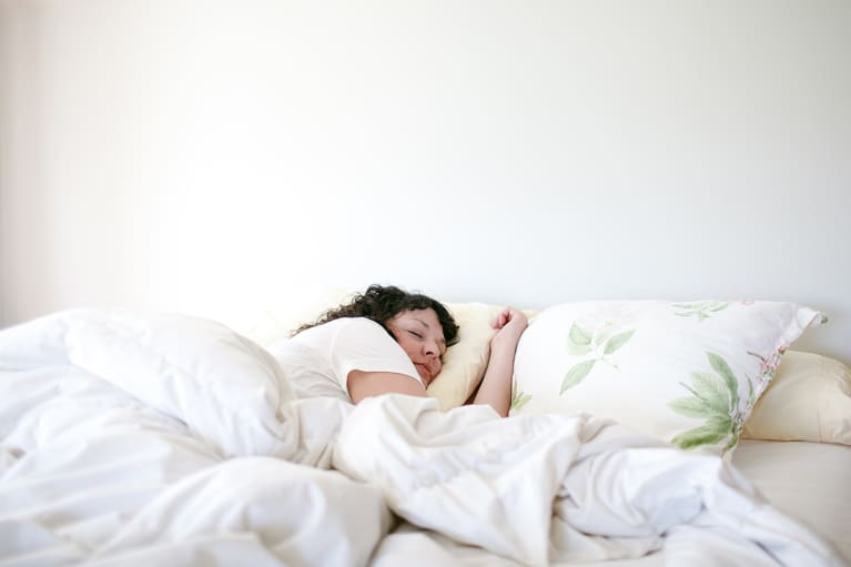 Woman Sleeping in white bedroom with plants on pillow