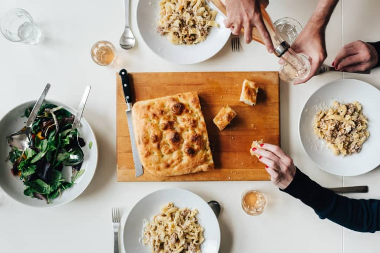 Overhead Photo of a Dinner Table with Pasta, Salad, and Focaccia