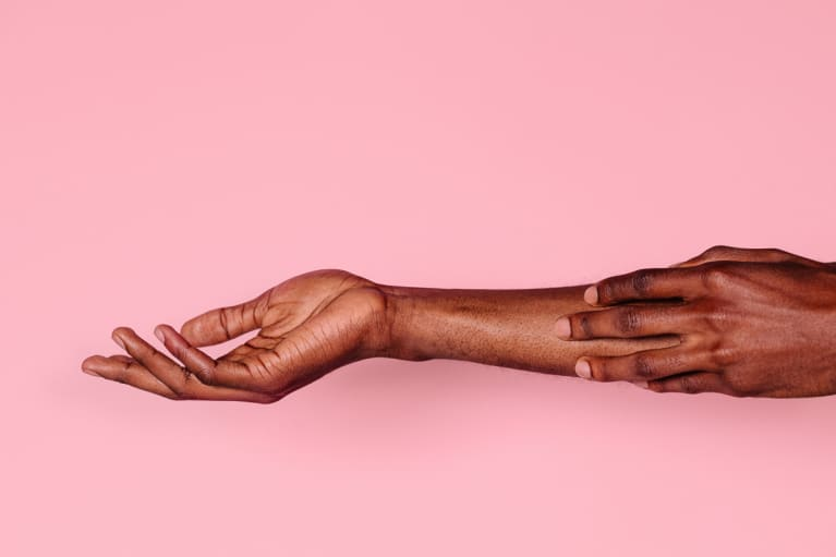 Man Touching His Forearm With Hand On Pink Background